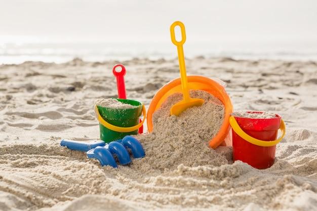 Drie emmers met zand en een spade op het strand Gratis Foto