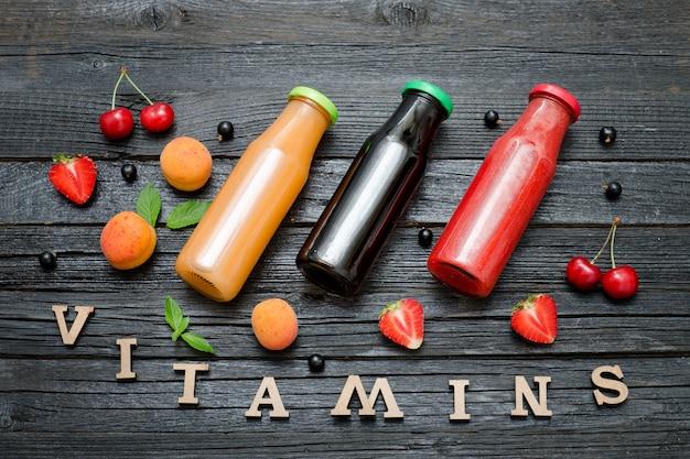 Drie flessen sap, fruit en inscriptie vitaminen. houten achtergrond. Premium Foto