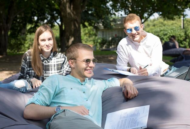 Drie gelukkige glimlachende studenten die in openlucht op een groot kussen ontspannen en hun huiswerk doen. Premium Foto