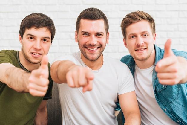 Drie gelukkige mannelijke vrienden die vinger naar camera richten Gratis Foto