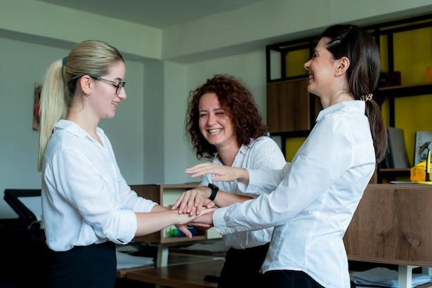 Drie gelukkige tevreden vrouwen kantoormedewerkers lachend vrolijk gestapeld hun handen gebaar van vriendschap, eenheid en partnerschap in het bedrijfsleven staan in kantoor Gratis Foto