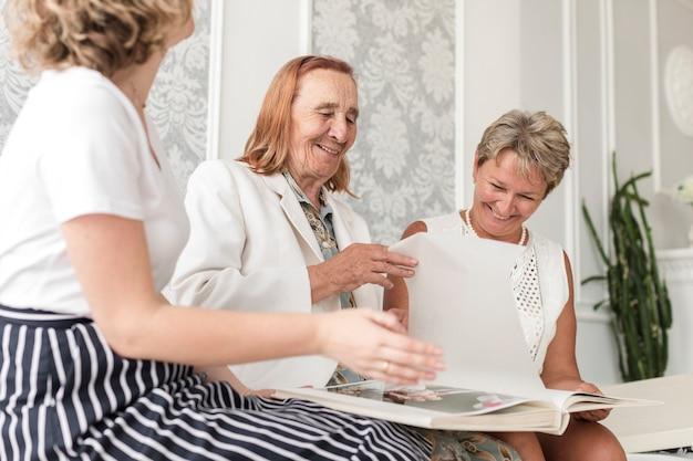 Drie generatievrouwen die samen zitten en fotoalbum thuis kijken Gratis Foto