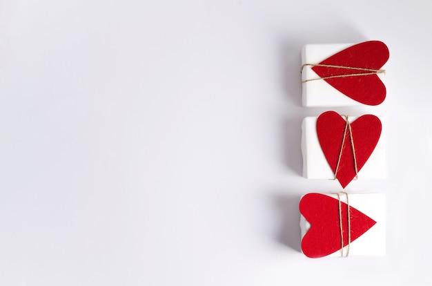 Drie geschenkdozen in wit papier en met hartjes liggen op een witte achtergrond. Premium Foto