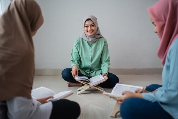 Drie gesluierde vrouwen zittend op de vloer tijdens het bestuderen van de koran Premium Foto