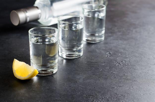 Drie glazen, een fles wodka, een stuk citroen op een donkere achtergrond. Premium Foto