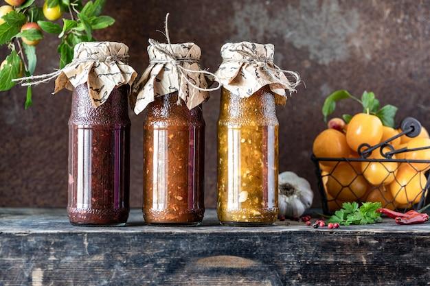 Drie glazen flessen geassorteerde georgische tkemali-saus met ingrediënten op rustieke houten tafel Gratis Foto