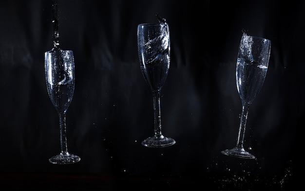 Drie glazen water op een zwarte achtergrond Gratis Foto