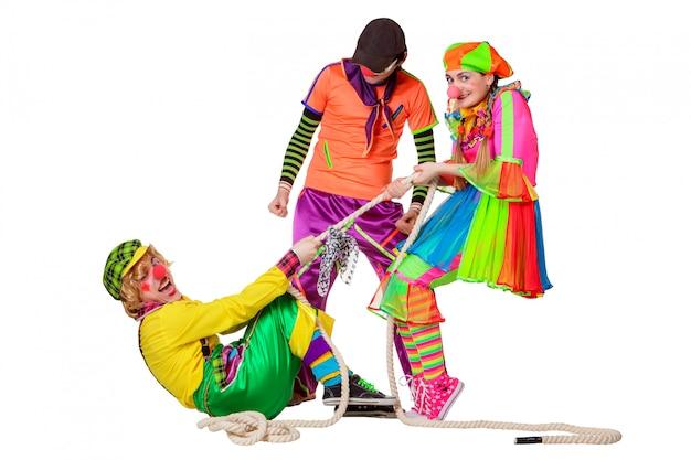 Drie glimlachende clowns met kabel die op de witte achtergrond wordt geïsoleerd Premium Foto