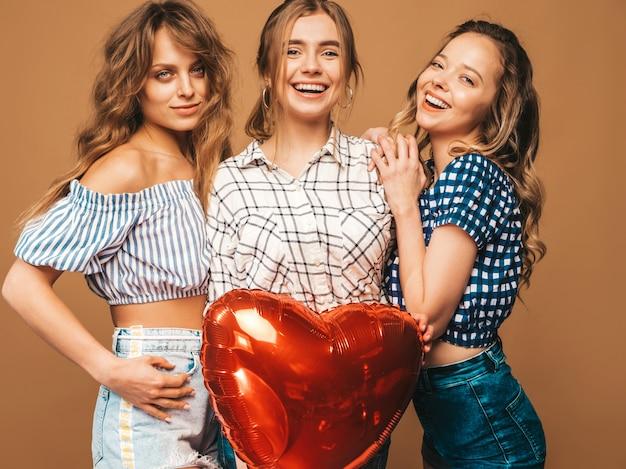 Drie glimlachende mooie sexy vrouwen in de kleren van de geruite overhemdszomer. meisjes poseren. modellen met hartvormige ballon. klaar voor valentijnsdag van de viering Gratis Foto
