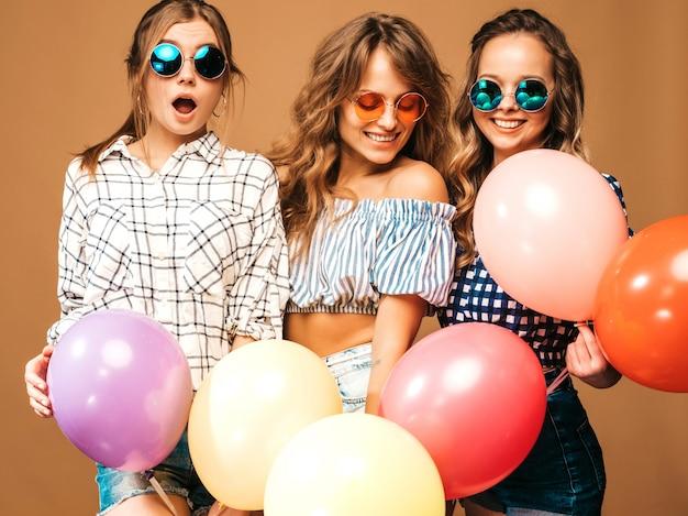 Drie glimlachende mooie vrouwen in de kleren van de geruite overhemdszomer. meisjes poseren. modellen met kleurrijke ballonnen in zonnebril. plezier, klaar voor de verjaardag van het feest Gratis Foto