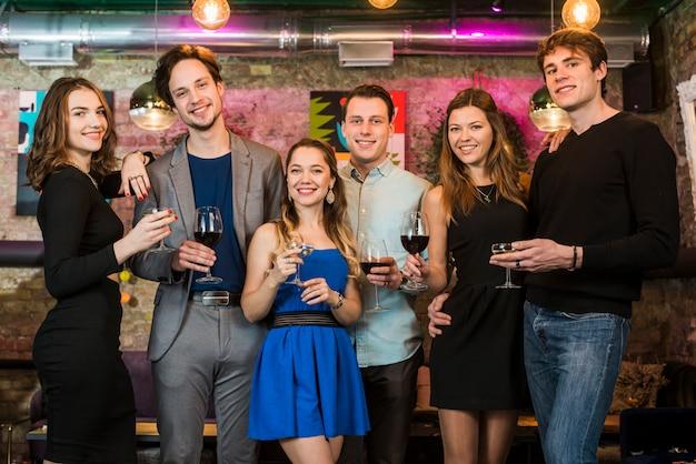 Drie glimlachende paren die avond van dranken in bar genieten Gratis Foto