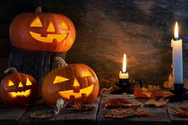 Drie halloween-pompoenen hoofdhefboom o lantaarn op houten lijst. Premium Foto