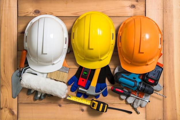 Drie helmen van oranje, geel en wit voor constructie en gereedschap. Premium Foto