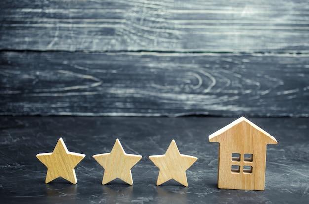 Drie houten sterren en een huis. drie sterren hotel of restaurant. herziening van de criticus. Premium Foto