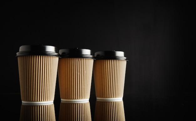 Drie identieke lichtbruine kartonnen afhaalkoffiekopjes met zwarte deksels op een rij op reflecterende zwarte tafel tegen zwarte muur Gratis Foto