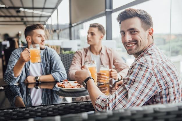 Drie jonge jongens zitten in een café en praten met glazen met bier over hun toekomst Premium Foto