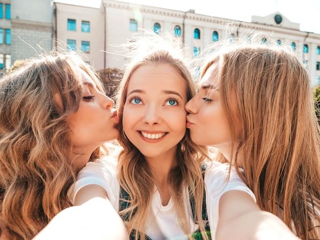 Drie jonge lachende hipster vrouwen in zomer kleding. meisjes selfie zelfportret foto's nemen op smartphone. modellen poseren in de straat. vrouwelijke kussen hun vriend in de wang Gratis Foto