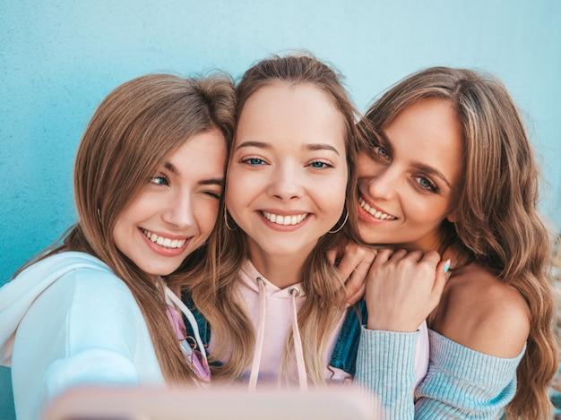 Drie jonge lachende hipster vrouwen in zomerkleren. meisjes nemen selfie zelfportret foto's op smartphone. modellen poseren in de straat in de buurt van muur. vrouwelijke tonen positief gezicht emoties Gratis Foto