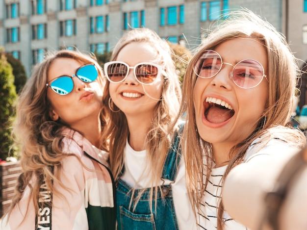 Drie jonge lachende hipster vrouwen in zomerkleren. meisjes nemen selfie zelfportret foto's op smartphone. modellen poseren in de straat. vrouw met positieve gezicht emoties in zonnebril Gratis Foto