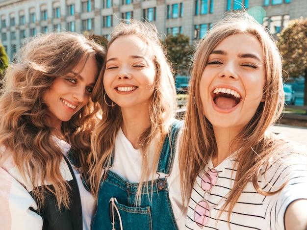 Drie jonge lachende hipster vrouwen in zomerkleren. meisjes nemen selfie zelfportret foto's op smartphone. modellen poseren in de straat. vrouwelijke tonen positief gezicht emoties Gratis Foto