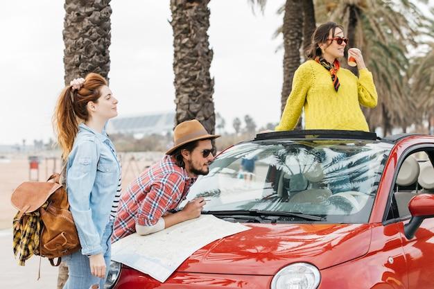 Drie jonge mensen die zich dichtbij auto met wegenkaart bevinden Gratis Foto