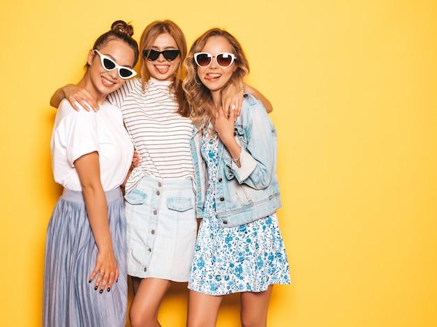 Drie jonge mooie glimlachende hipster meisjes in trendy zomerkleren. sexy onbezorgde vrouwen die dichtbij gele muur stellen. positieve modellen die pret in zonnebril hebben Gratis Foto