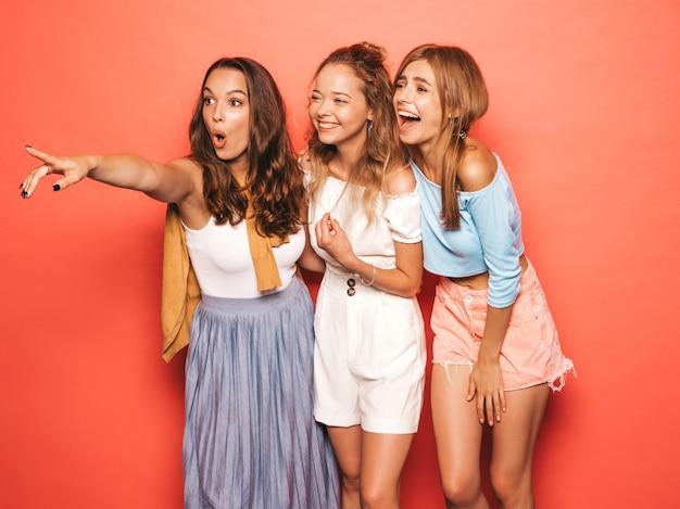 Drie jonge mooie glimlachende hipster meisjes in trendy zomerkleren. sexy onbezorgde vrouwen die dichtbij roze muur stellen. positieve modellen met plezier. aandacht voor winkelverkopen Gratis Foto