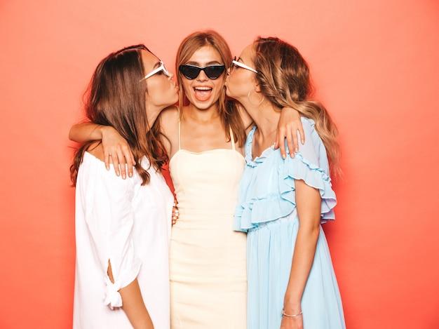 Drie jonge mooie glimlachende hipster meisjes in trendy zomerkleren. sexy onbezorgde vrouwen die dichtbij roze muur stellen. positieve modellen worden gek en hebben plezier. hun vriend op de wang kussen Gratis Foto
