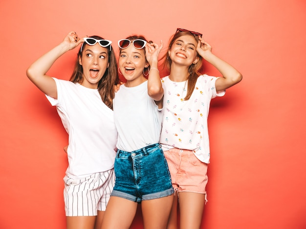 Drie jonge mooie glimlachende hipster meisjes in trendy zomerkleren. sexy onbezorgde vrouwen die dichtbij roze muur stellen. positieve modellen worden gek en hebben plezier Gratis Foto