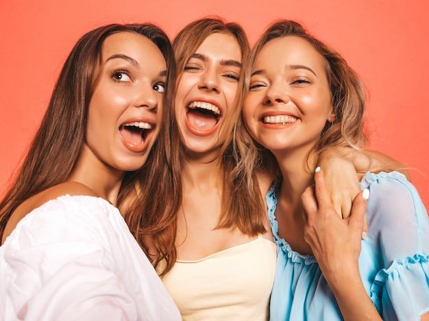 Drie jonge mooie glimlachende hipster meisjes in trendy zomerkleren. sexy onbezorgde vrouwen die dichtbij roze muur stellen. positieve modellen worden gek. zelfportretfoto's maken op smartphone Gratis Foto