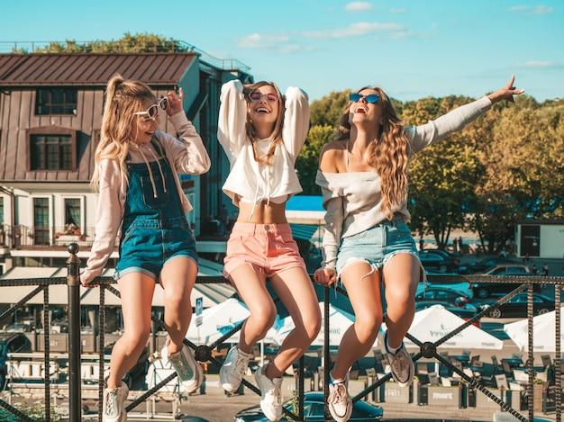 Drie jonge mooie glimlachende hipster meisjes in trendy zomerkleren Gratis Foto