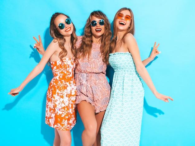 Drie jonge mooie glimlachende meisjes in trendy zomer casual jurken en in zonnebril. sexy zorgeloze vrouwen poseren. Gratis Foto