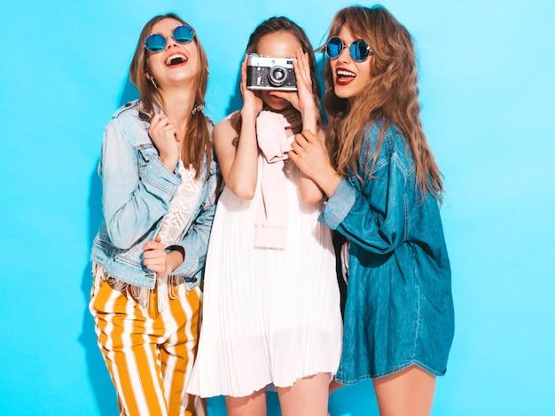 Drie jonge mooie glimlachende meisjes in trendy zomer kleurrijke jurken en zonnebrillen. sexy zorgeloze vrouwen poseren. foto's maken met een retro camera Gratis Foto