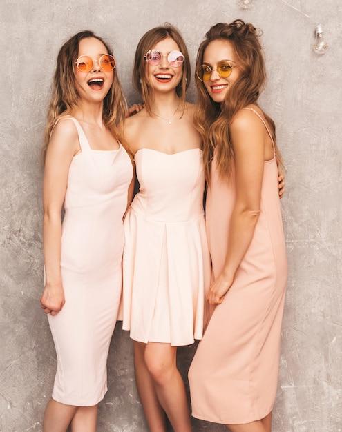 Drie jonge mooie glimlachende meisjes in trendy zomer lichtroze jurken. sexy zorgeloze vrouwen poseren. positieve modellen in ronde zonnebril met plezier Gratis Foto
