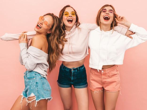 Drie jonge mooie glimlachende meisjes in trendy zomerkleren. sexy zorgeloze vrouwen poseren. positieve modellen hebben plezier Gratis Foto