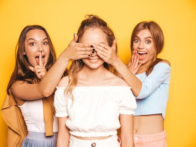 Drie jonge mooie lachende hipster meisjes in trendy zomerkleding. sexy zorgeloze vrouwen poseren in de buurt van gele muur. modellen verrassen hun vriend. ze bedekken haar ogen en knuffelen van achteren Gratis Foto