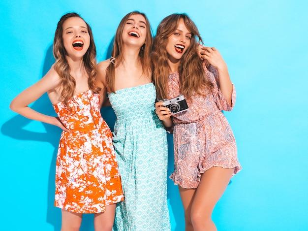 Drie jonge mooie lachende meisjes in trendy zomer casual jurken. sexy zorgeloze vrouwen poseren. foto's maken met een retro camera Gratis Foto
