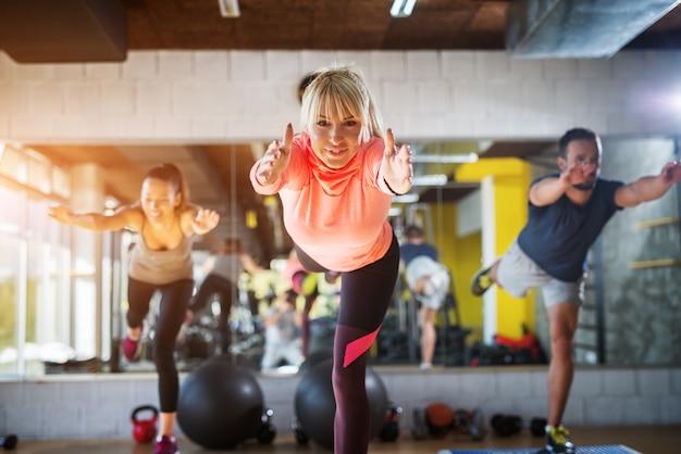 Drie jonge sportieve mensen werken aan hun evenwichtsvaardigheden terwijl ze op één been staan met gestrekte handen voor zich. Premium Foto