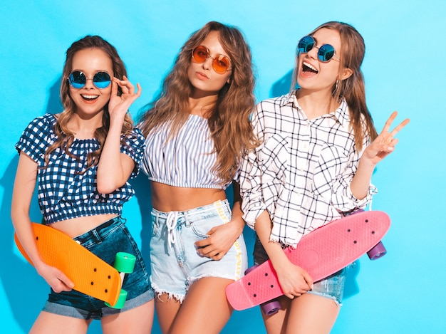 Drie jonge stijlvolle lachende mooie meisjes met kleurrijke penny skateboards. vrouwen in zomer kleding poseren in zonnebril. positieve modellen hebben plezier Gratis Foto