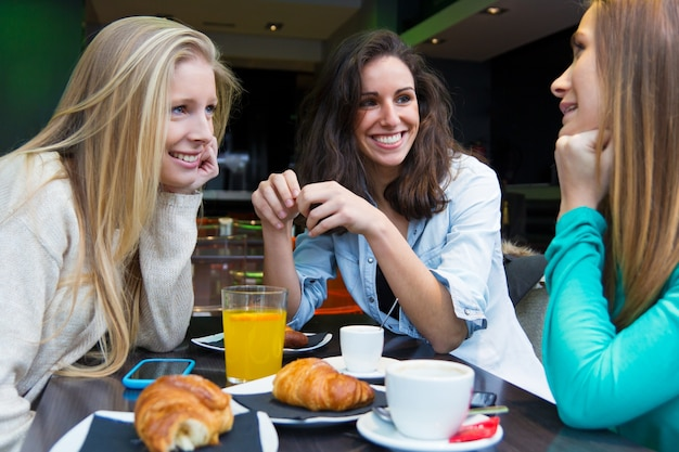 Drie jonge vrienden hebben ontbijt op een ochtend winkelen in de stad Premium Foto