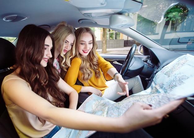 Drie jonge vriendinnen reizen in een auto Premium Foto