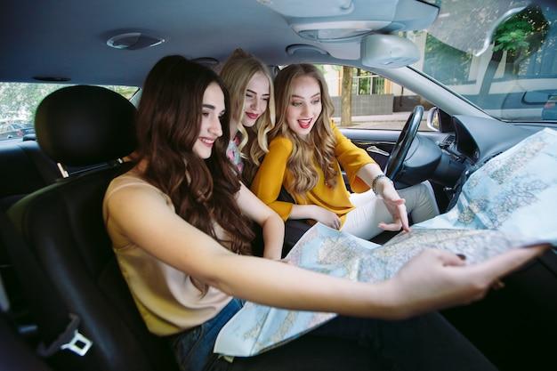Drie jonge vriendinnen reizen in een auto. Premium Foto