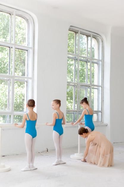 Drie kleine ballerina's dansen met persoonlijke balletleraar in dansstudio Gratis Foto