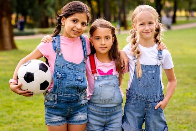 Drie kleine meisjes poseren voor de camera in het park Gratis Foto