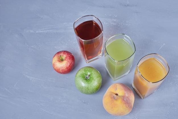 Drie kopjes verschillende vruchtensappen. Gratis Foto
