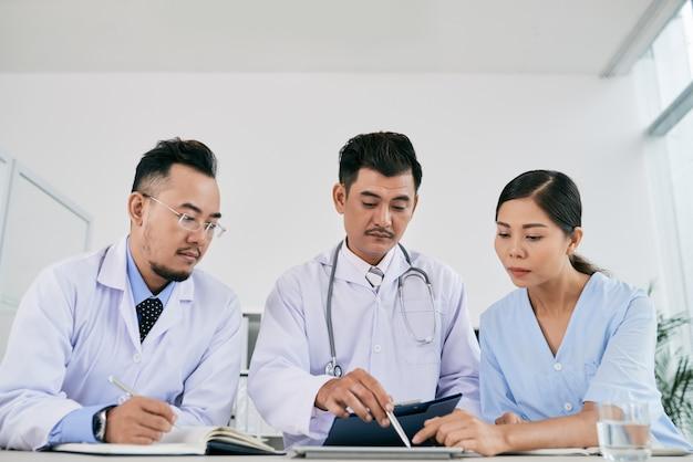 Drie mannelijke en vrouwelijke medische professionals die de medische geschiedenis van de patiënt bespreken Gratis Foto