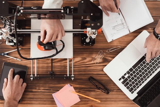 Drie mannen werken aan het maken van een 3d-printer. Premium Foto