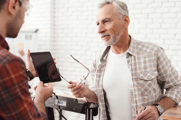 Drie mannen zetten een zelfgemaakte 3d-printer op om het formulier af te drukken. Premium Foto