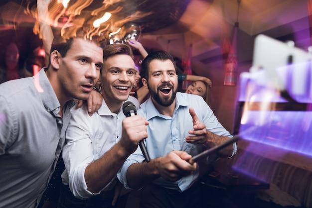 Drie mannen zingen in karaokeclub. mensen hebben plezier in nachtclub Premium Foto