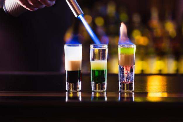 Drie meerlagige brandende cocktail. de barman steekt ze lichter aan. Premium Foto